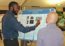 Odelmo Joseph explains his UVI research project Saturday to symposium judge and math instructor Celik Ekici.