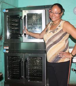 Gladys Abraham Elementary Principal Lisa Hassell-Forde seems excited about her school's new oven. (Photo provided by V.I. Department of Education)