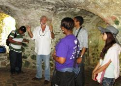 Historian David Knight with the V.I. Scholars program students inside the lower level of the Estate Catherineberg windmill.