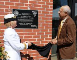 Rear Adm. Cindy Covell and Alton Adams Jr. unveil plaque naming a Navy band building for Alton Adams Sr.