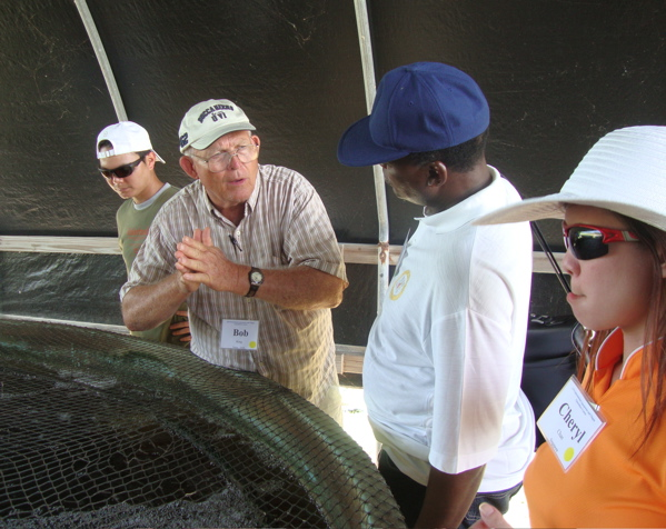 International participants talk around a tank of tilapia during the 12th Annual International Aquaponics and Tilapia Aquaculture Course.