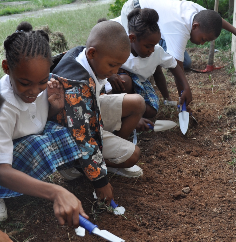 Students from Claude O. Markoe Elementary get ready to plant spinach in the school's first garden bed.