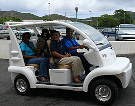 Carl Christensen of the U.S. Small Business Administration takes a solar SunBug vehicle for a spin Friday with Jewel Linzey, Karen Jane and Roman Richardson.