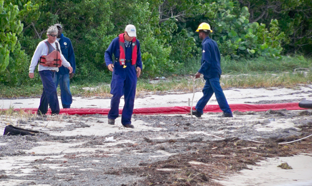 A WAPA crew assesses the fuel spill on the sand near the Estate Richmond dock. (Carol Buchanan photo)