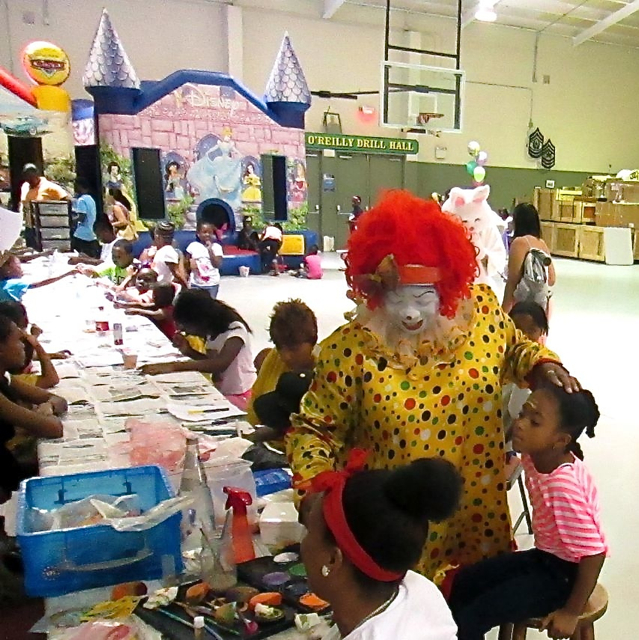 Ann Jerris as JayJay the Clown paints the face of 6 year-old A'Jiydah Schuster while other kids do craft projects and others play in the bouncy structures.