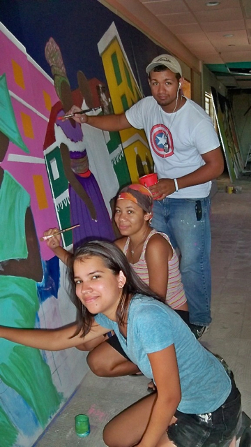 From bottom up, Katherine Bishop, Cherise Finney and Victor Cepeda paint the parade mural.