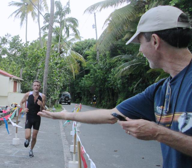 First-place men's triathlon finisher Brent Lynn approaches volunteer Bern Putnam.