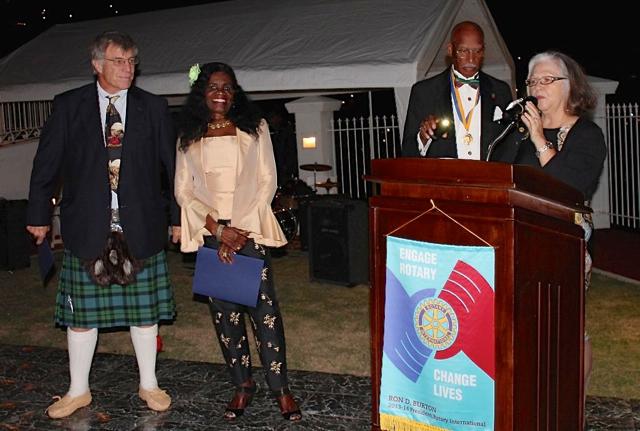 Shaun Pennington, president of Rotary Sunrise, honors her club's Harris awardees, Mike McKay, left, and Lynn Igwemadu.