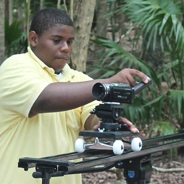 YMW student Michael D. Brown of Wesleyan Academy rigs the camera on a dolly dolly for a tracking shot. (Jae Knight photo)
