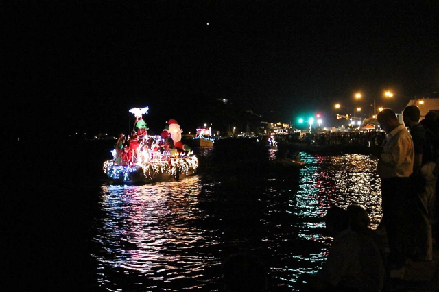 Lighted boat parade entries sailing along the St. Thomas waterfront.