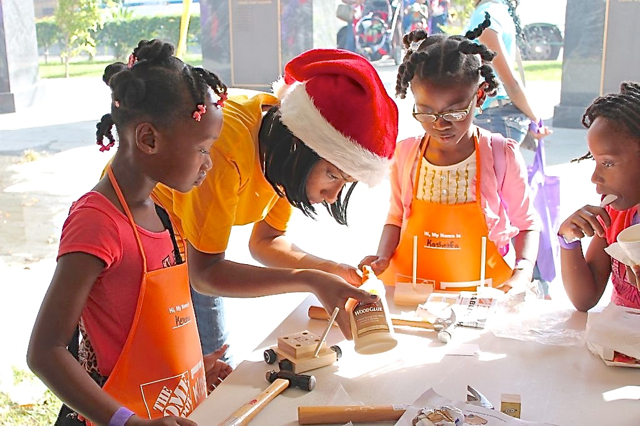 'Santa Helpers' lend a hand as youngsters build toys in the Home Depot Kids' Workshop section.