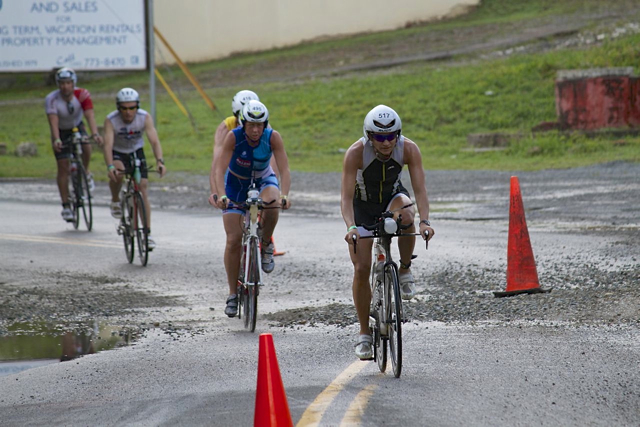 Racers carefully navigate a stretch of gravel-strewn roadway. Debris washed out by rain felled many riders.
