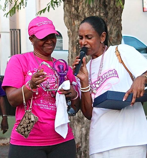 Cancer survivor Raynette Cameron, left, receives an award from ACS executive director Lorraine Baa.