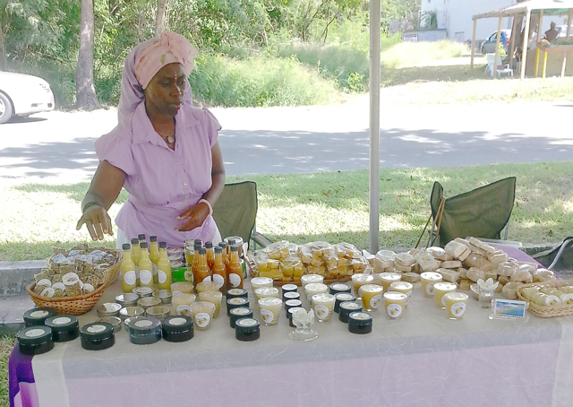 Violet Drew displays a tableful of honey and beeswax products at the Beekeepers' Buzzaar.