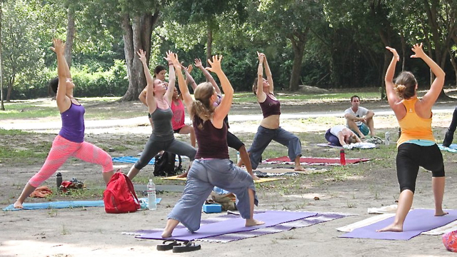 Yogis perform sun salutation postures.