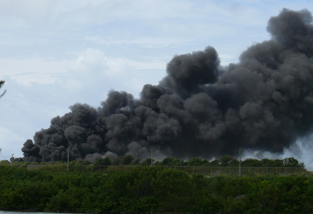 A massive, billowing cloud of black smoke pours into the air above the Hovensa refinery.