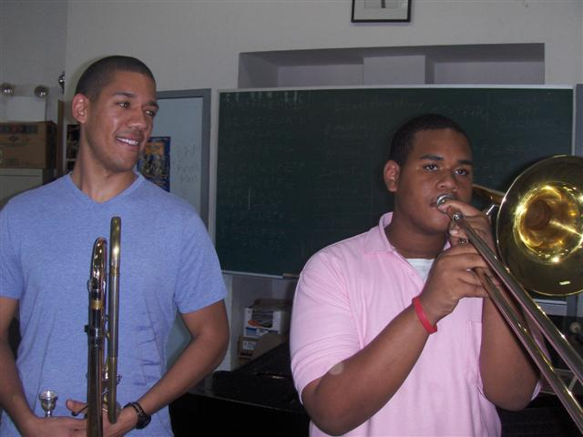 Renowned trombonist Weston Sprott (left) smiles appreciatively as student musician Juan Martinez plays.