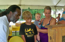 Errol Chichester (left) explains the workings of the hive to Anders Olson as his mom Karen Olson holds brother Osten.
