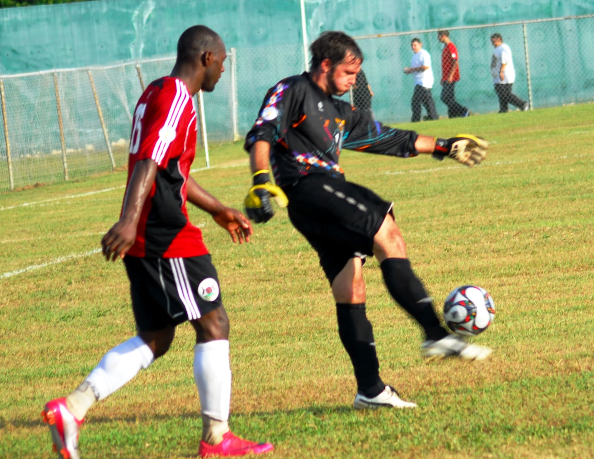 V.I. goalkeeper Dillon Pieffer (right) being shadowed by Antigua and Barbuda's Peter Byers.