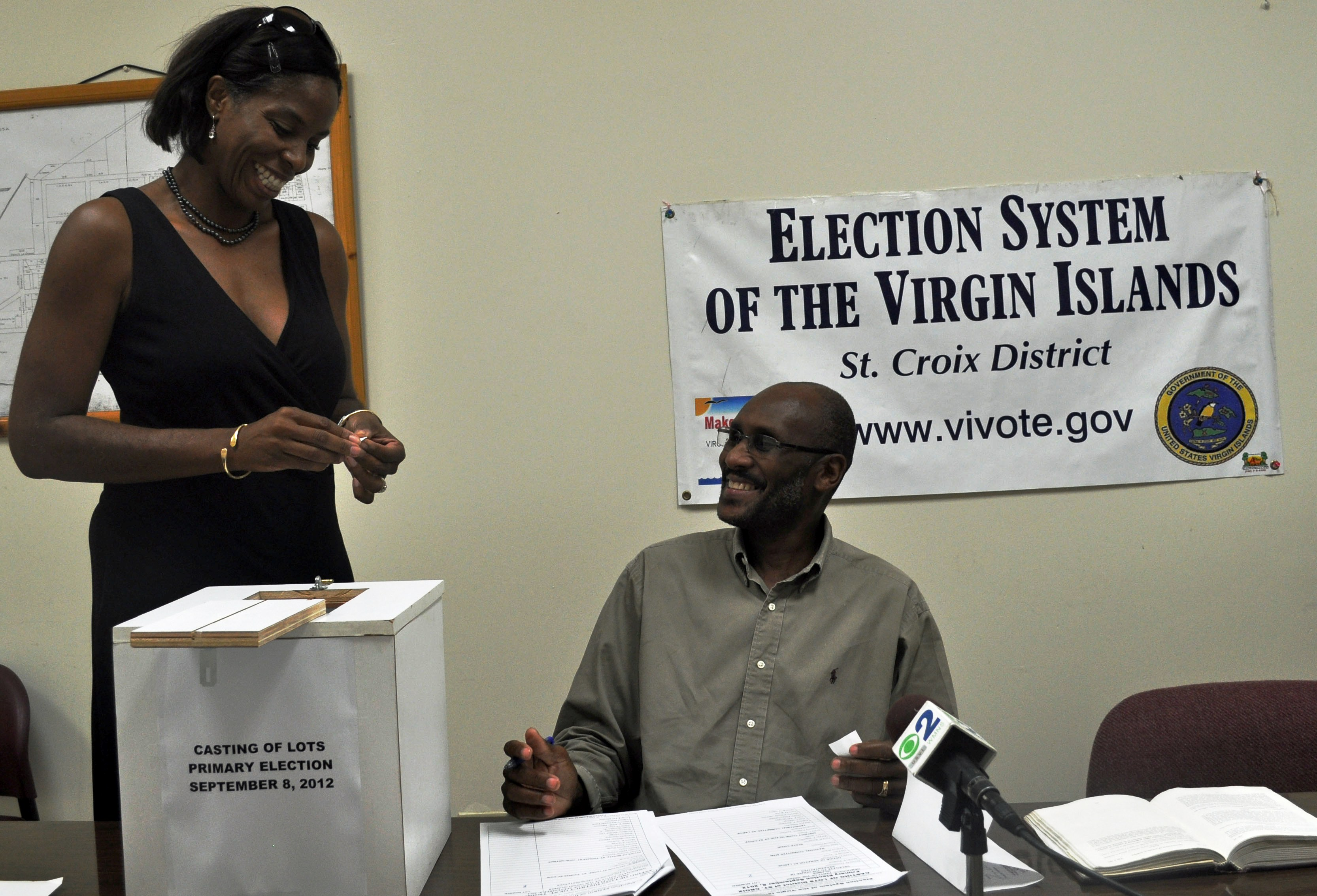 Stacey E. Plaskett , Democratic candidate for delegate to the U.S. House of Representatives, reaches into the box Tuesday during the casting of lots on St. Croix as Supervisor of Elections John Abramson Jr. awaits her number.
