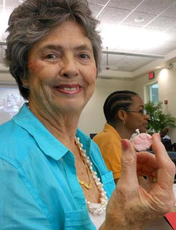 Entrepeneur Ivanne Farr holding a brooch made from local conch at her studio.