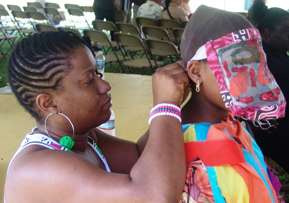 Trina Roper adjusts the masquerade costume of her 9-year-old daughter, Aniya.