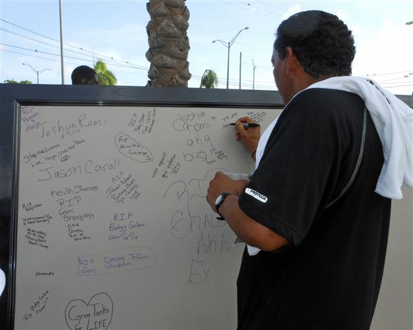 A runner leaves a message on the memorial board Sunday.