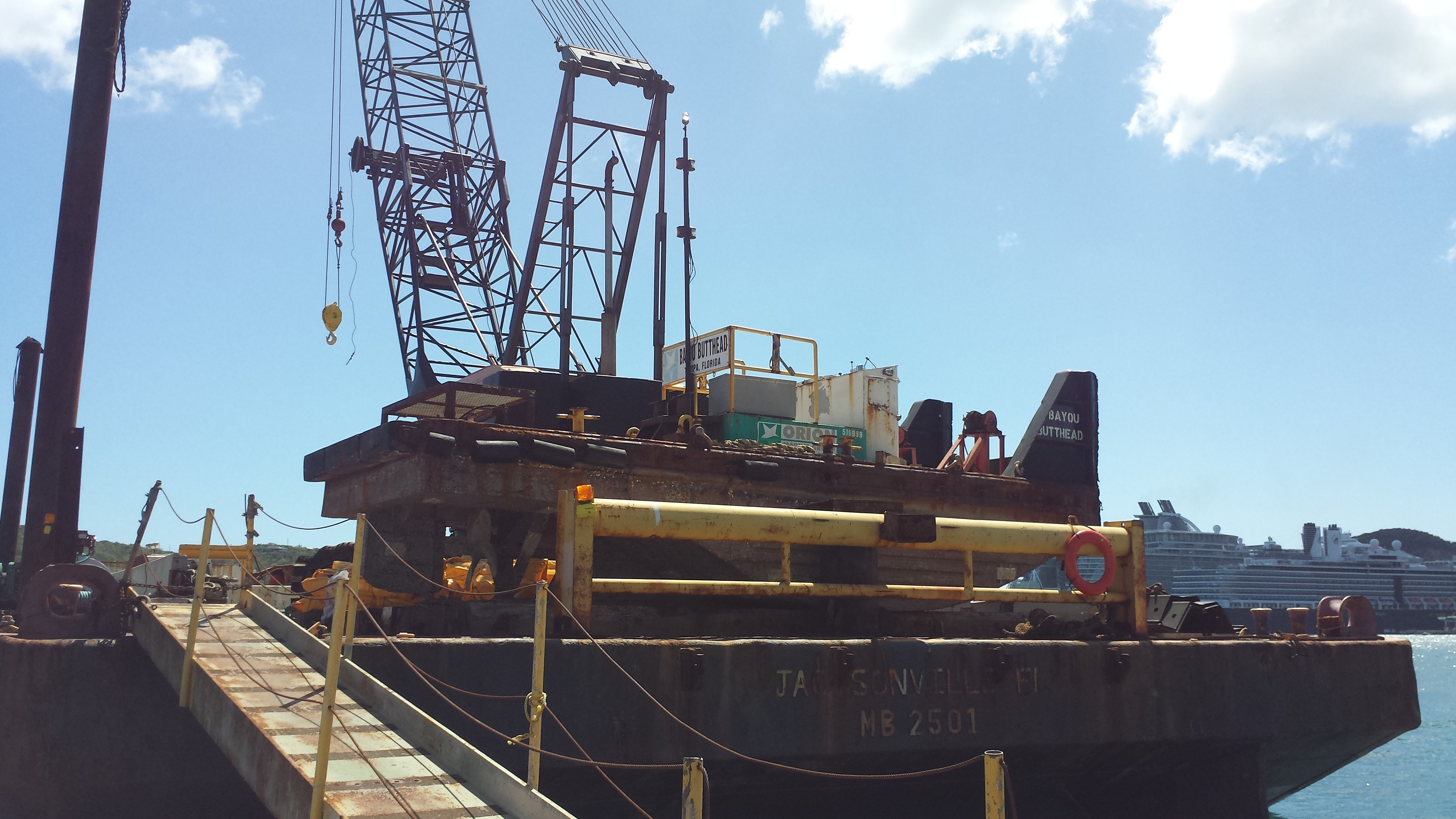 The barge operated by Orion Marine Construction Inc. is stationed in Crown Bay as workers prepare the silt curtain to begin dredging.