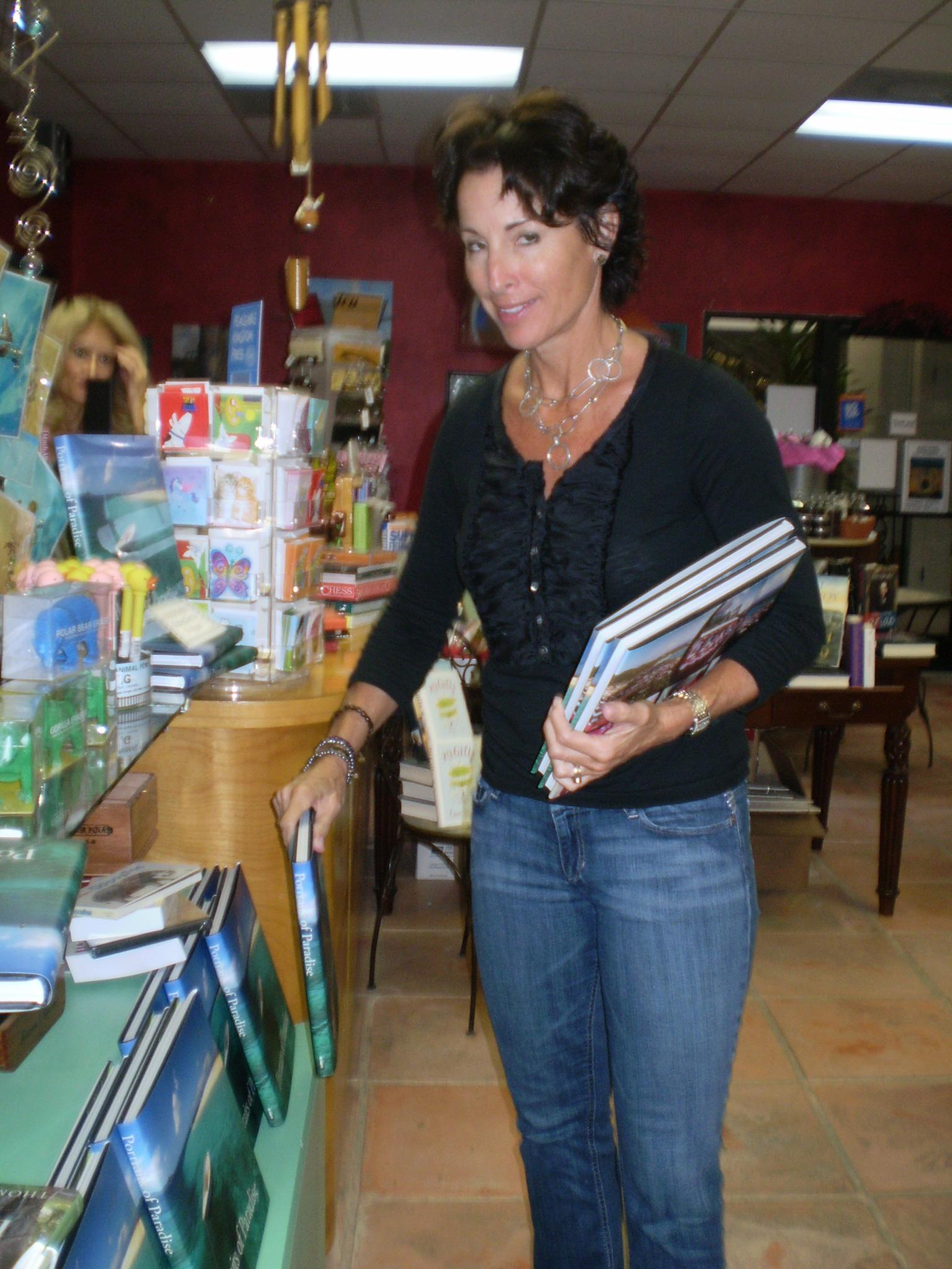 "Undercover Books owner Kathy Bennett stocking ""Portraits of Paradise."""