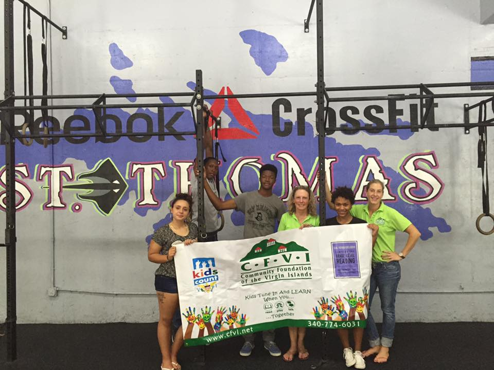Crossfit St. Thomas volunteers help to distribute books to young children.