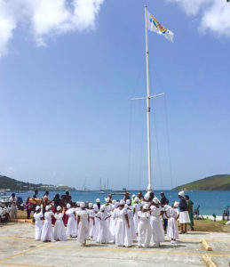 The Ulla F. Muller Bamboula Dancers watch as the V.I. flag is lowered during African Liberation Day opening ceremonies. It was replaced for the day by the Pan African flag. (Photo by Augustine Holder)