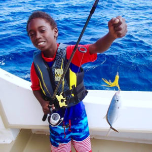 Joseph Wilson shows off his catch on a Marine Vocational Program outing. (Photo by Jimmy Loveland.)