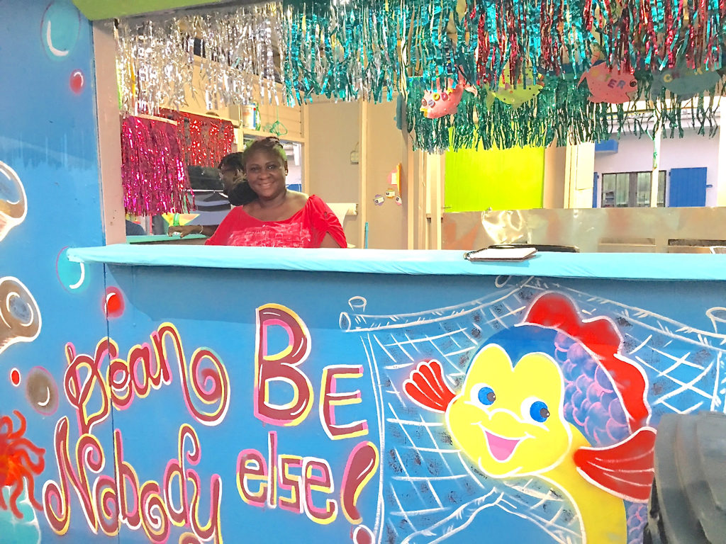 """Claudine Scatliffe Daniel at the """"Doan Be Nobody Else' food booth at the St. John Festival Village."""