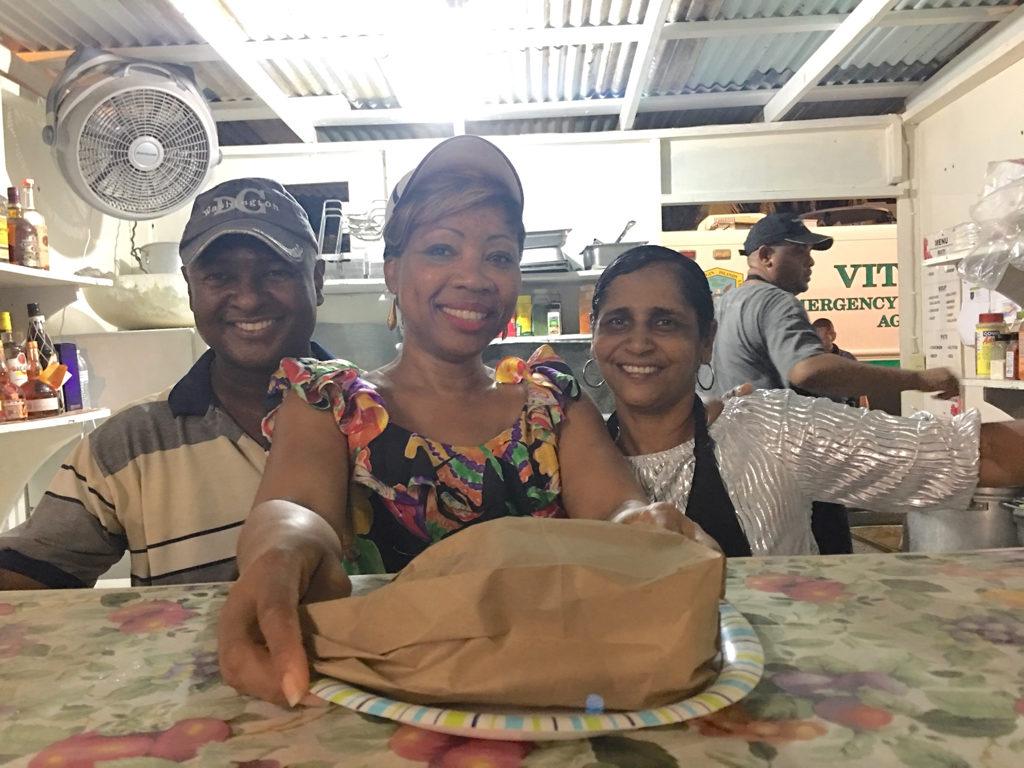 Fitzroy Douglas, Diane Lewis, and Leah Rivière serve roti made by chef Troy Ferguson