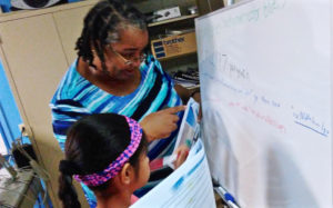 Anita Davis works with a student at 'Code Like A Girl' camp Wednesday. (Photo provided by V.I. Next Generation Network)