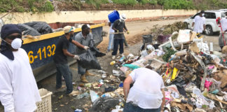 Residents work together Thursday to clean up trash piles in the hurricane-battered Tutu Hi-Rise Housing Community.