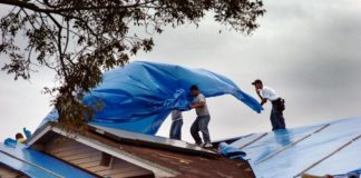Operation Blue Roof workers install tarps on storm-damaged homes in the territory. (Source file photo)