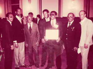 "McIntosh receives an award from the National Endowment of the Arts with band members Meg Gordon, Isidore Griles, Frank Charles, Lloyd Thomas, Sylvester ""Blinky"" McIntosh, Anselmo Clarke and Gustave Petersen."