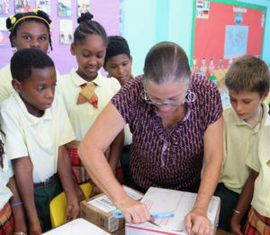 Fourth grade teacher Lisa Magras opens a box of school supplies for her class at Pearl B. Larsen Elementary School. (Photo from the V.I. Department of Education)
