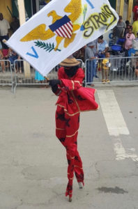 A moko jumbie waves a 'V.I. Strong' banner while marching Saturday. (Photo by Jess Parker)