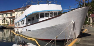 Saltaire, partly aground at Cruz Bay Creek, cannot be lifted until it is cleaned.