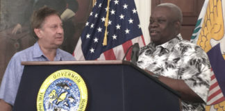 Jonathan Cohen accepts check on behalf of JKC Family from Gov. Kenneth Mapp at a Feb. 7 news conference. (Marina Leonard photo)