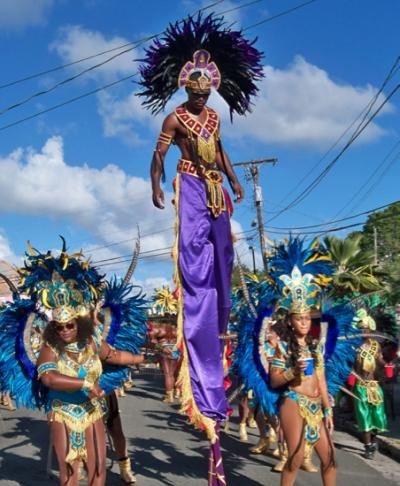 A stilt dancer towers over the parade