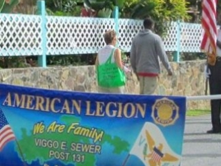 Marcelle Whitney and Doug Benton carry the American Legion banner