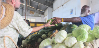 Dale Brown of Sejah Farms sells locally grown produce to a customer.