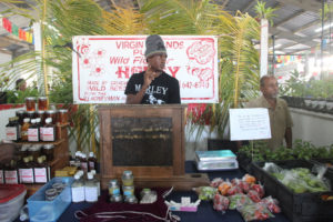 "Roniel Allembert II keeps beekeeping in the family by assisting his father known as the ""V.I. Honeyman"" with his booth."