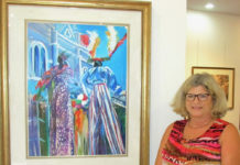 Melia Cook of the St. Thomas Historical Trust poses with Marsha Stein's painting of mocko jumbies at the exhibition in Yacht Haven Grand. It will be open through Saturday.