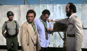 In a scene from 'The In-Laws,' corrupt Gen. Garcia of Tijada bestows medals on Peter Falk and Alan Arkin. Shortly afterwards he orders them executed.