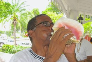 Steve Isaac of the Pan-African Support Group blows the conch shell on July 3, 2014. (Source file photo)