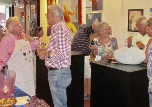 Frank Machover, left, extols the virtues of a cool, crisp rose' in the tropical climate. Third from right, Chantal charms guests at a Mango Tango wine tasting.